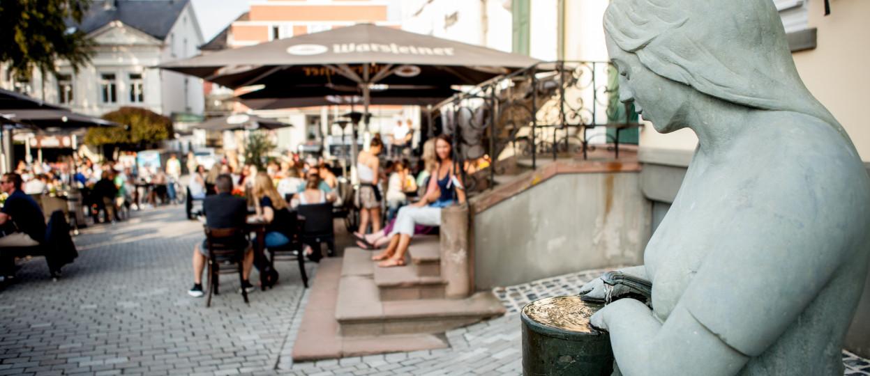 Das Bild zeigt die Statue einer Marktfrau. Sie hält einen Krug mit Wasser. Im Hintergrund sitzen einige Menschen in den Biergärten der Gastwirtschaften am Markptlatz.