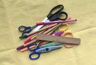 Bild mit beigem Hintergrund zeigt Bastelmaterial, Scheren, Stifte, Lineal, die auf einem Haufen liegen.