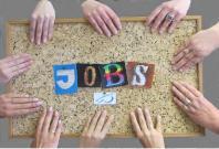 """Das Bild zeigt eine Pinnwand. Auf dieser steht in bunten Buchstaben """"Jobs"""". Viele Hände halten die Pinnwand am Rand fest."""